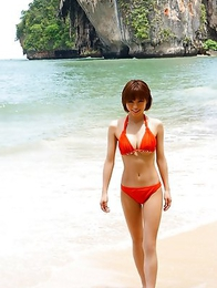 Japanese Yumiko Shaku  in orange bath suit takes a walk on the beach